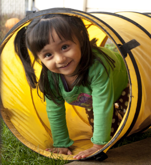 Small girl smiling and siting playfully in a pipe